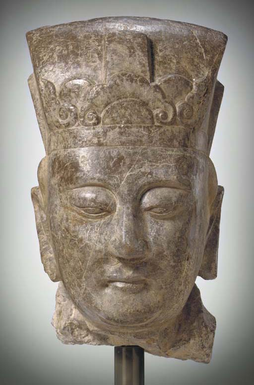 A LARGE BROWNISH STONE HEAD OF