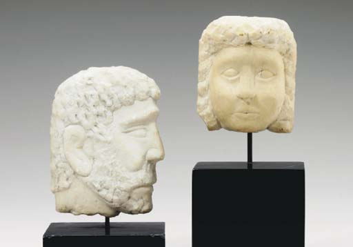 FOUR CARVED MARBLE MASKS,