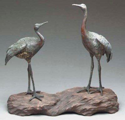 A PAIR OF BRONZE CRANES ON A G