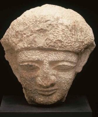 AN EGYPTIAN LIMESTONE HEAD FRO