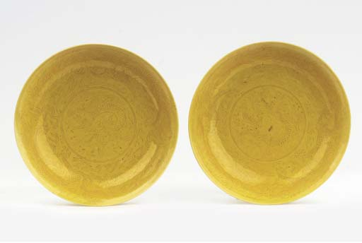 A pair of yellow-glazed saucer
