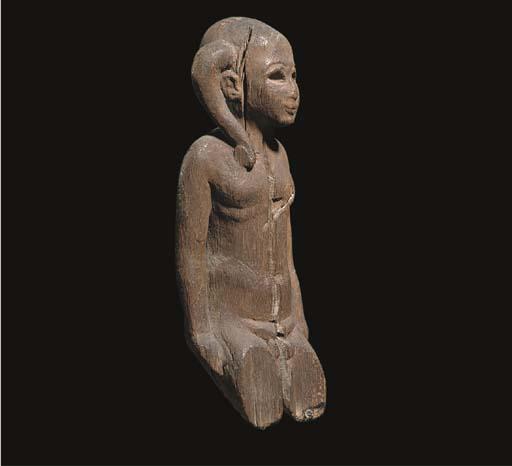 AN EGYPTIAN WOOD FIGURE OF HARPOCRATES