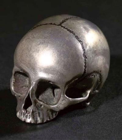 A silver netsuke of a skull, 1