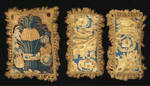A tapestry cushion, faced with a border fragment woven with a column of flowers--17½ x 12½in. (45 x 32cm.), probably 18th century with later fringing and velvet backing; a pair of tapestry cushions woven with golden foliate scrolls against a blue ground, with similar later mounting; and an Aubusson style tapestry cushion woven with a basket of flowers within an oval foliate surround--21 x 19½in. (53 x 50cm.), 19th century with later pale blue moiré mount