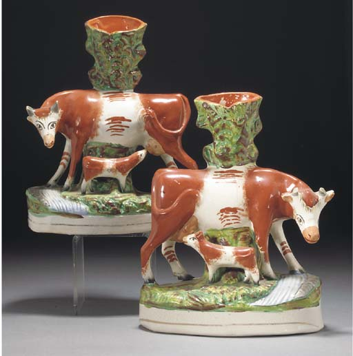 Two Staffordshire pottery cow