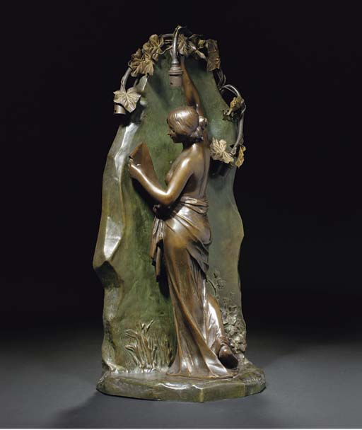 A patinated spelter figural ta
