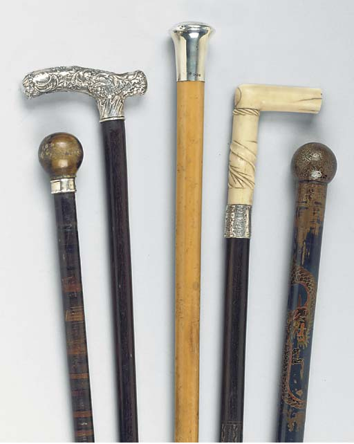 A GROUP OF FIVE WALKING STICKS