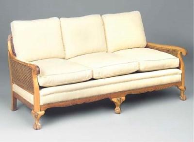 A carved walnut and caned sofa