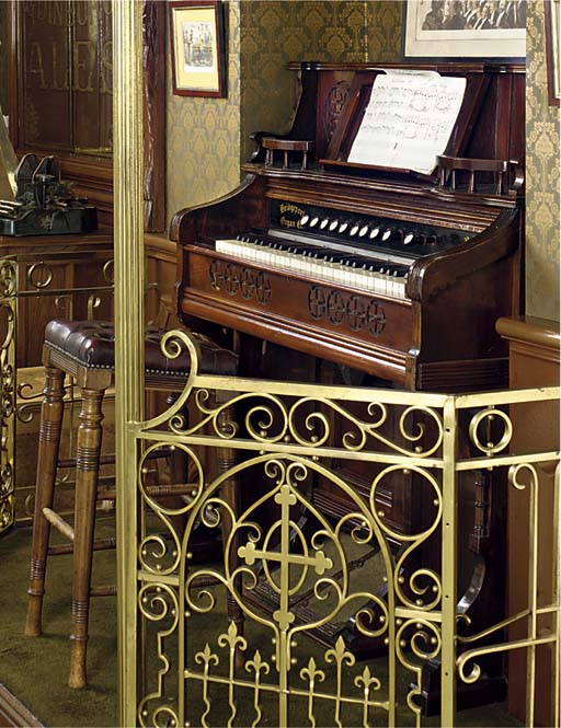 A WALNUT CASED HARMONIUM