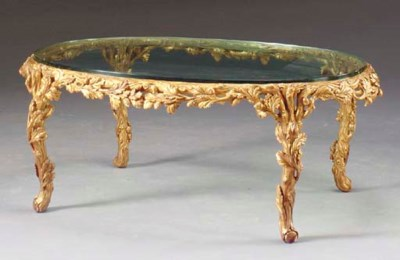 A CARVED GILTWOOD OVAL GLASS T