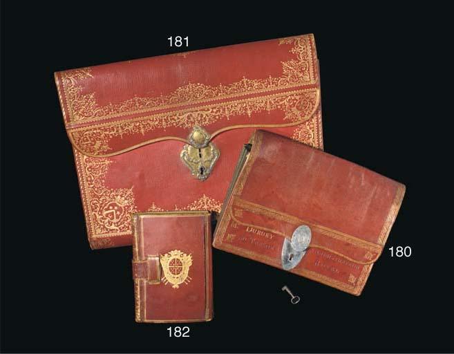 PORTEFEUILLE DU CONTRÔLEUR GÉNÉRAL DES FINANCES DE LOUIS XVI. (335 x 447 mm). Maroquin rouge dans le goût de Derome, large dentelle à l'oiseau (fers à l'oiseau de deux sortes) bordée de filets droits et dentés, le fond du portefeuille décoré comme un dos lisse à filets gras et maigres et large fleuron répété, doublure du rabat décorée d'une dentelle florale et libellules, l'extréméité du rabat à semé de fleurs tigées, doublure intérieure de soie bleu ciel, cordon de même (décousu à l'une des extrémités, complet), serrure à deux plaques de cuivre à décor repoussé, gravée aux armes de Louis Gabriel TABOUREAU DES RÉAUX (1718-1782, Olivier 337). (Fond partiellement décousu ou déchiré, quelques taches et égratignures, sans la clef.)