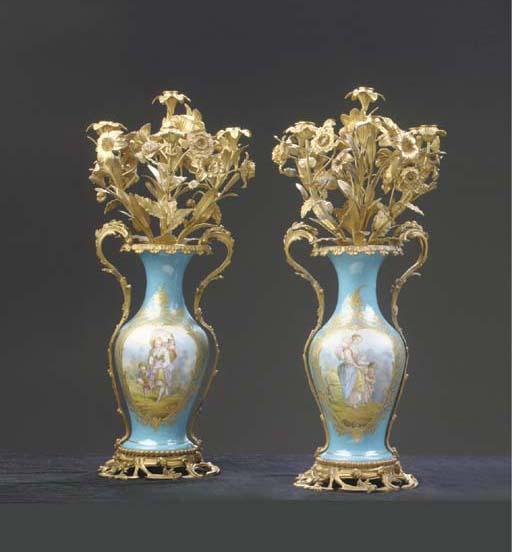 A pair of Sevres-style porcelain gilt metal-mounted floral candelabra-topped baluster ornamental vases