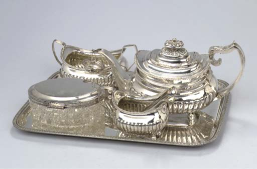 A George III silver three-piece tea service with a German silver tray, a Dutch silver-mounted cut-glass biscuit box and a pair of sugar tongs