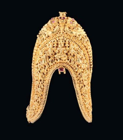A GOLD ORNAMENT INSET WITH RUB