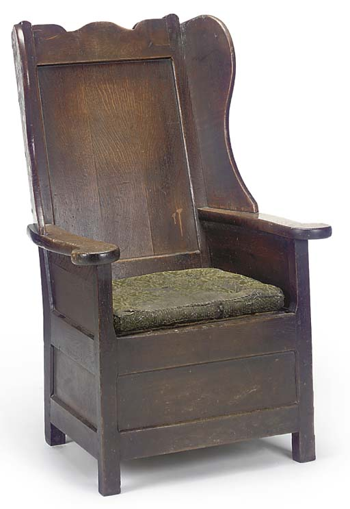 AN OAK WING ARMCHAIR