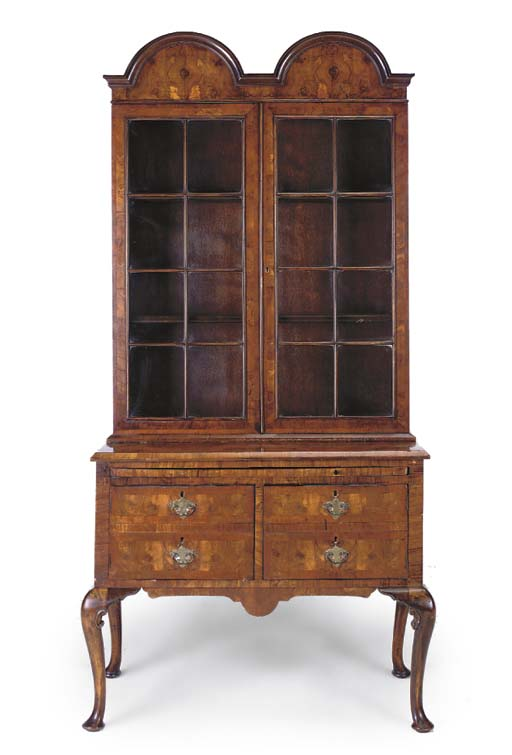 A WALNUT DISPLAY CABINET ON ST