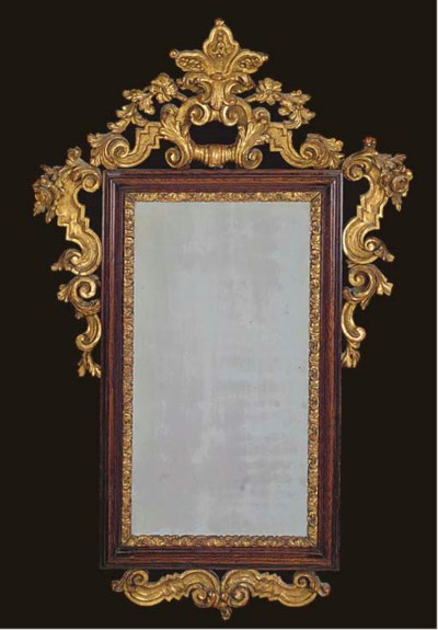 AN OAK AND CARVED GILT MIRROR