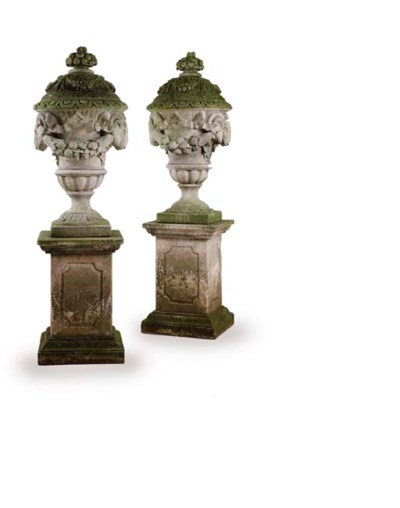 A PAIR OF CARVED STONE URNS ON