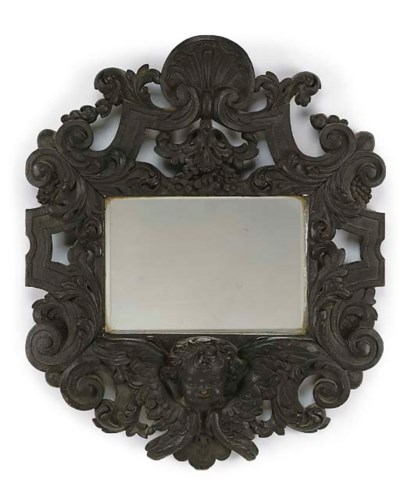 A CARVED OAK MIRROR