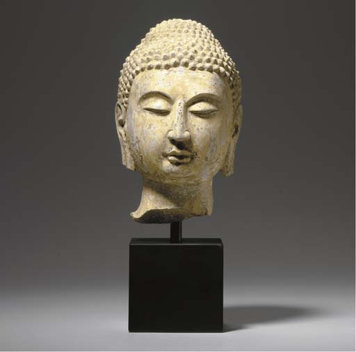A SMALL PAINTED DARK GREY STONE HEAD OF BUDDHA