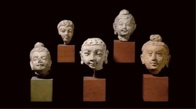 A group of five stucco heads