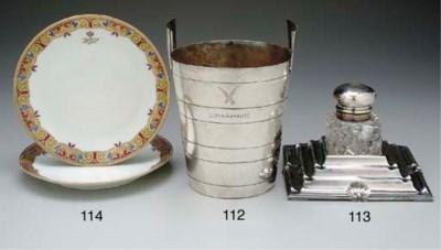 an ice bucket in silver-plate