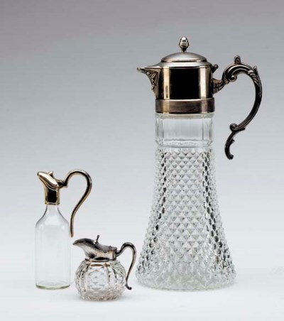 FOUR GLASS PITCHERS WITH SILVE