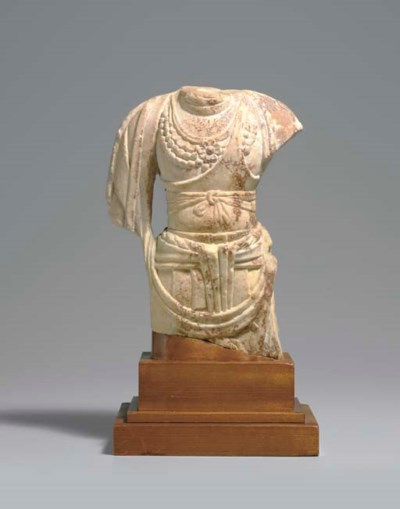 A SMALL WHITE MARBLE TORSO OF
