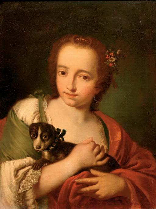 A young woman in a green dress and a red wrap, with a dog in her arms