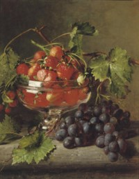Strawberries in a glass bowl with grapes on a ledge
