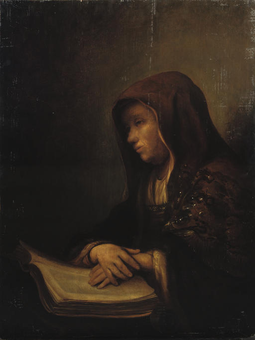 An old woman seated at a table with her hands resting on an open book