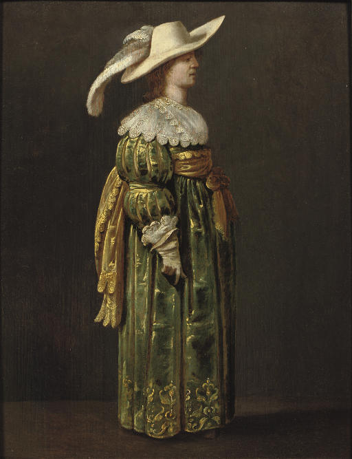 An elegant woman, full-length, standing in profile, in a green and gold embroidered dress and feathered hat