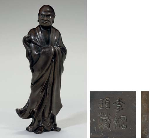 A silver-inlaid bronze figure