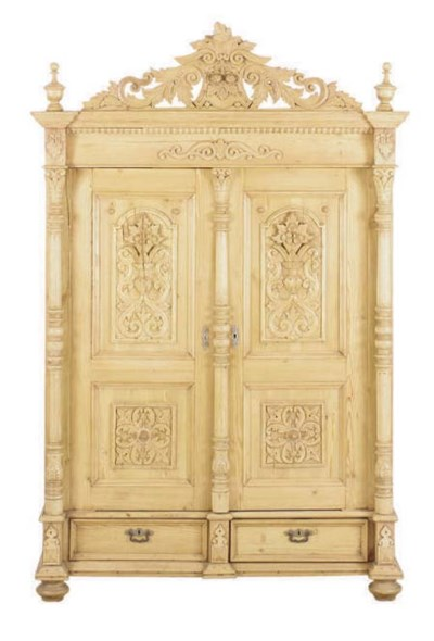 A CARVED PINE TWO-DOOR ARMOIRE