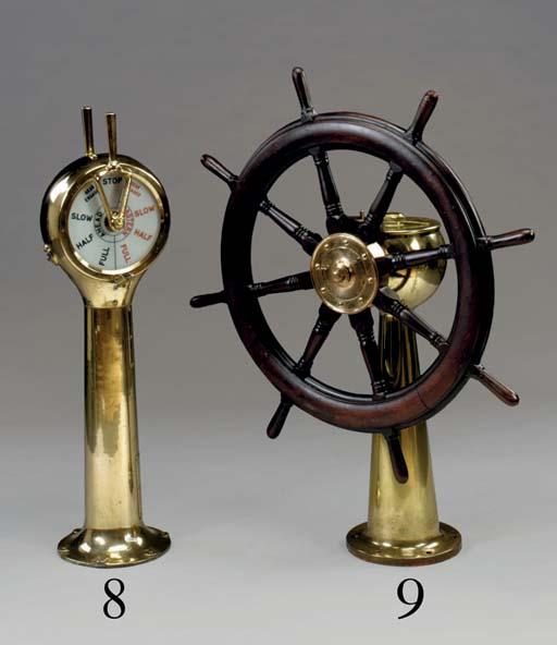 An eight spoke mahogany ship's wheel on a bronze pedestal