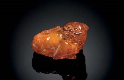 A SMALL AMBER CARVING OF A CAT