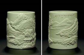 A RARE PALE LIME GREEN-GLAZED CARVED PORCELAIN BRUSHPOT