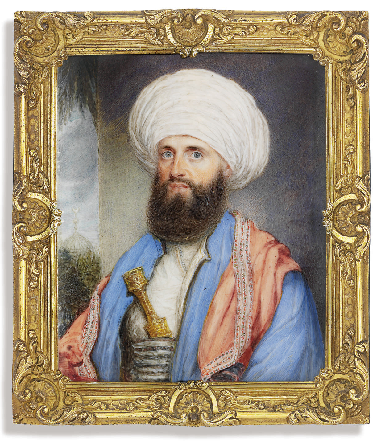 James Silk Buckingham (1786-1855), in white shirt with a light blue coat, pink embroidered shawl around his shoulders and a white turban with a dagger secured in to his cummerbund; landscape background with a mosque