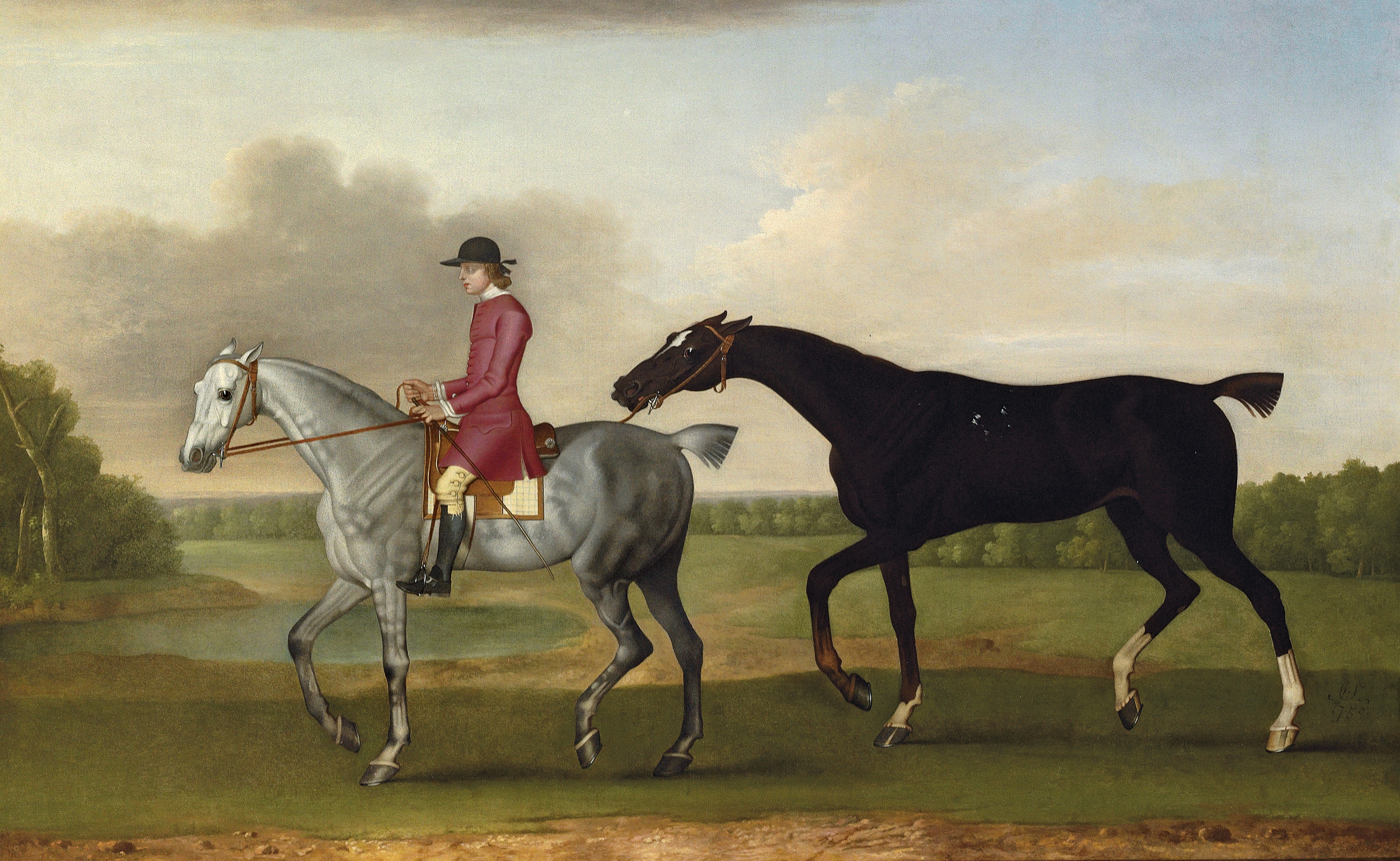 A liver chesnut racehorse led by a mounted groom in a wooded landscape