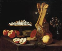 Sweets on a tazza, narcissi in a glass vase, breadsticks in a jar, and apples, jelly and a lemon on a draped table