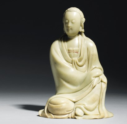 A CARVED SOAPSTONE SEATED FIGU