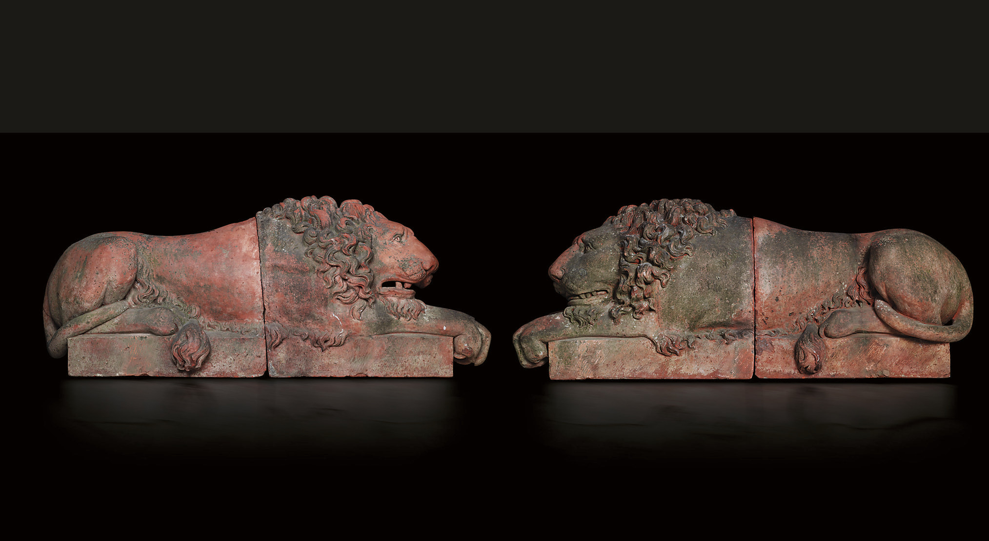 A PAIR OF RECLINING TERRACOTTA LIONS
