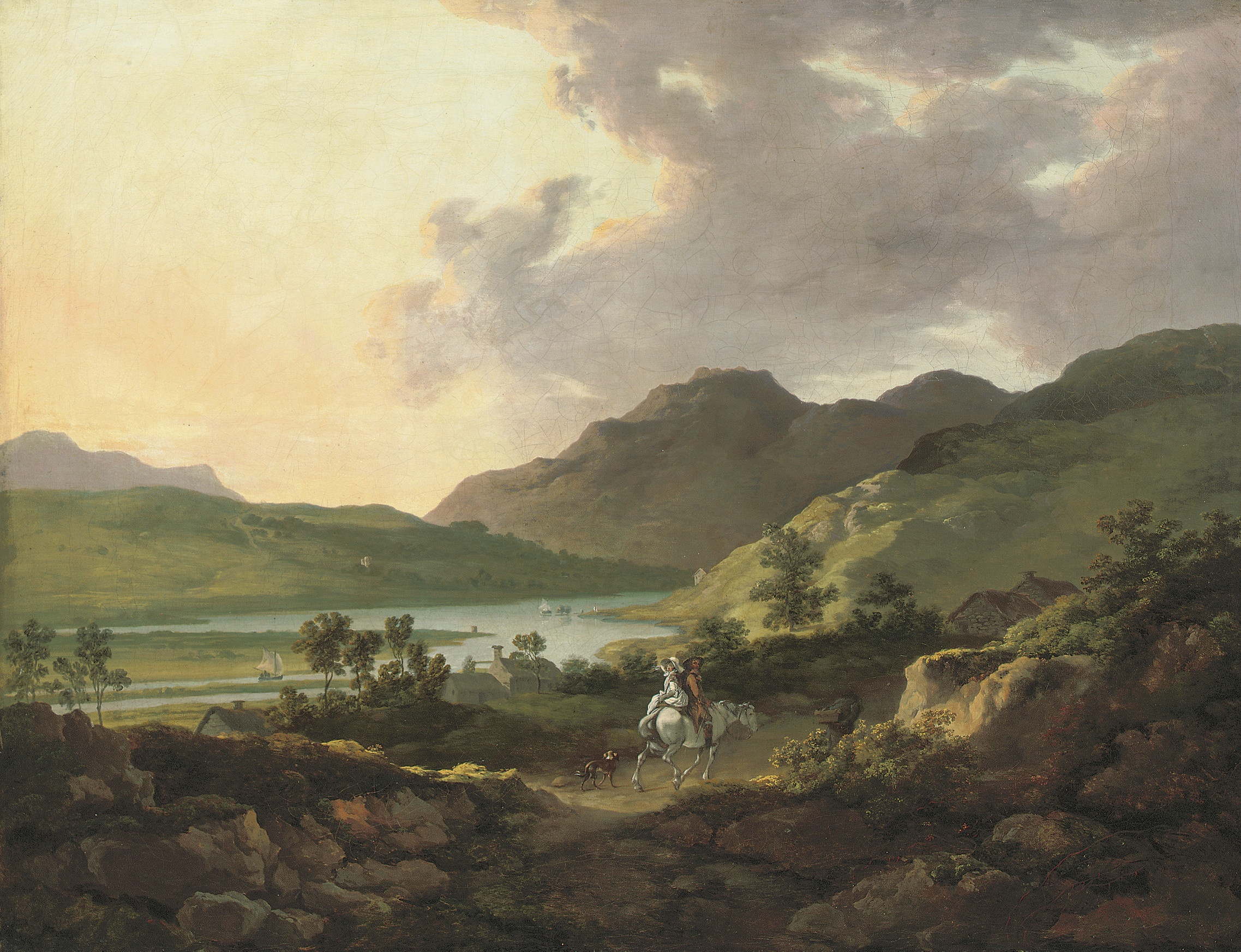 A mountainous lake landscape with travellers on a path in the foreground and boats on the lake beyond