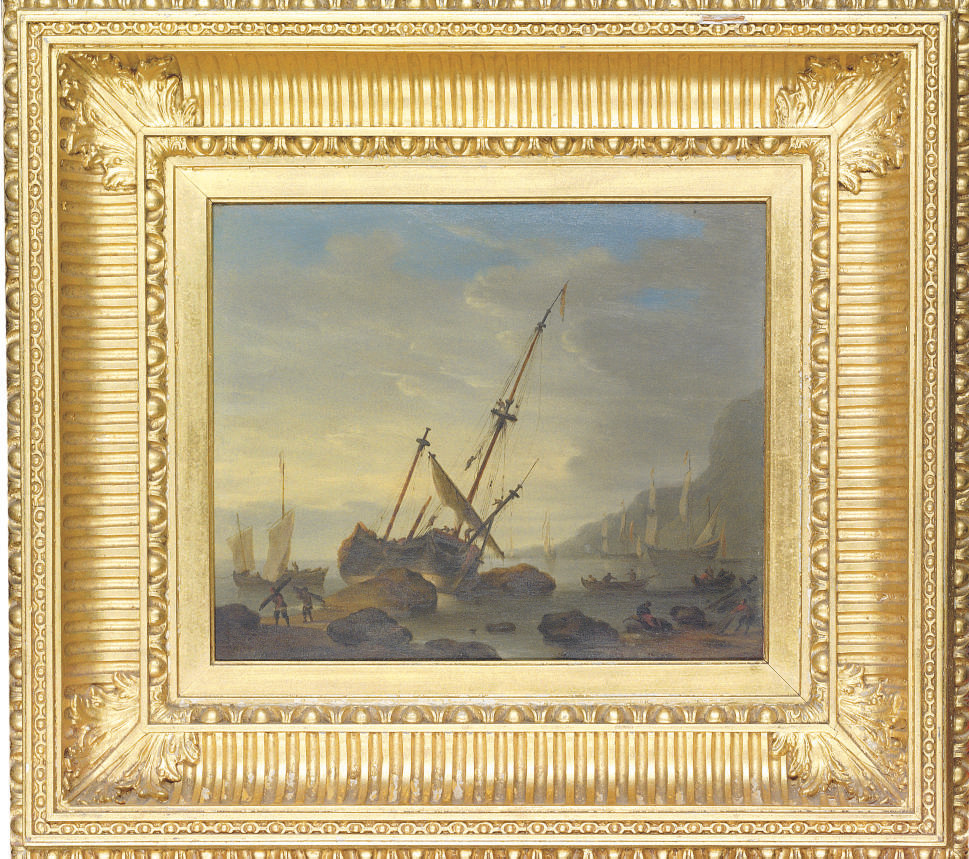 A coastal landscape with a sailing ship run aground