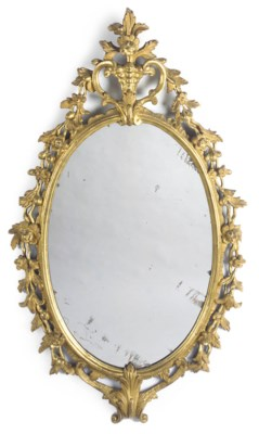A CARVED GILTWOOD OVAL MIRROR