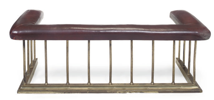 A BRASS AND LEATHER UPHOLSTERE