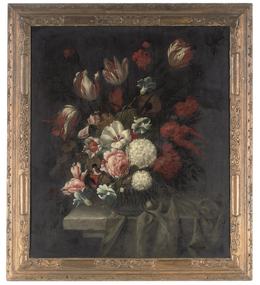 Roses, parrot tulips, white hydrangea and other flowers in a glass vase on a stone ledge with drapery