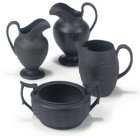 THREE SHORTHOSE BLACK BASALT MILK-JUGS AND A SUGAR-BOWL