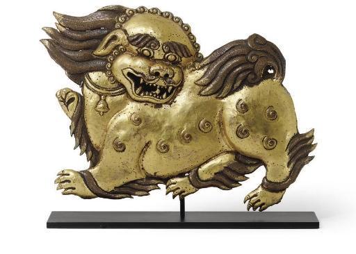 A gilt copper repousse lion pl