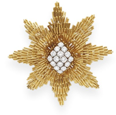 A DIAMOND AND GOLD STAR BROOCH